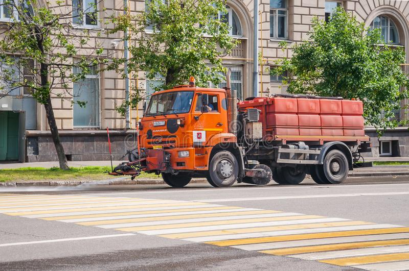 KAMAZ car watering machine with water tank washes asphalt in dry summer weather. MOSCOW, RUSSIA - July 1, 2019: KAMAZ car watering machine with water tank washes royalty free stock photo
