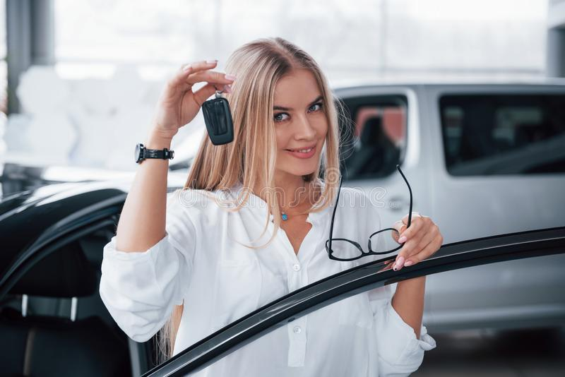 With keys in hand. Cute girl in eyewear stands near the car in auto saloon. Probably her next purchase.  royalty free stock images