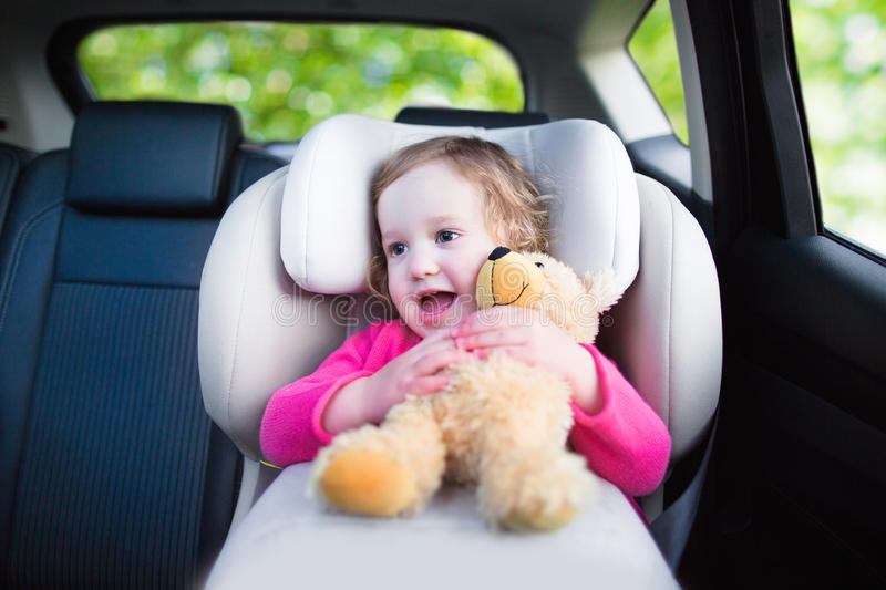 Little girl in car seat. Cute curly laughing and talking toddler girl playing with a toy bear enjoying a family vacation car ride in a modern safe vehicle stock photo