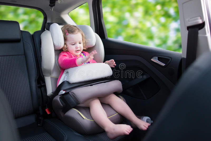 Little girl in car seat. Cute curly laughing and talking toddler girl playing with a toy enjoying a family vacation car ride in a modern safe vehicle sitting in stock photos