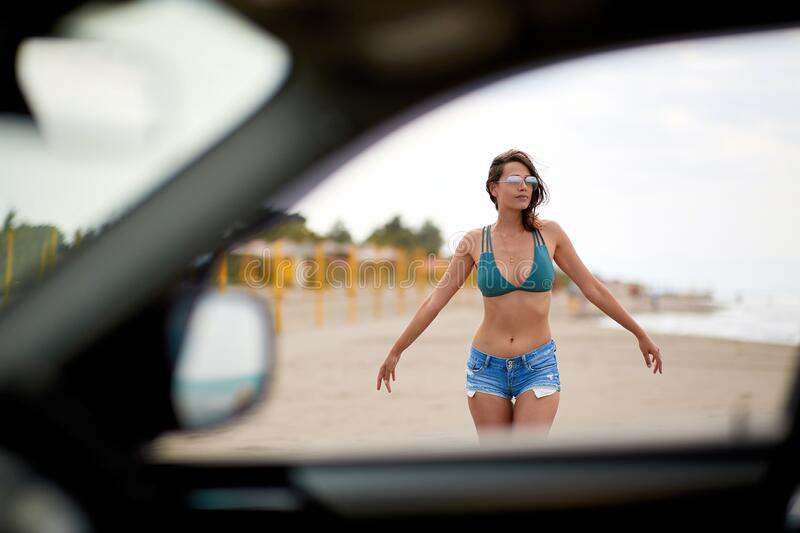 A look at sexy girl on a beach through car window. Enjoying the sun stock images