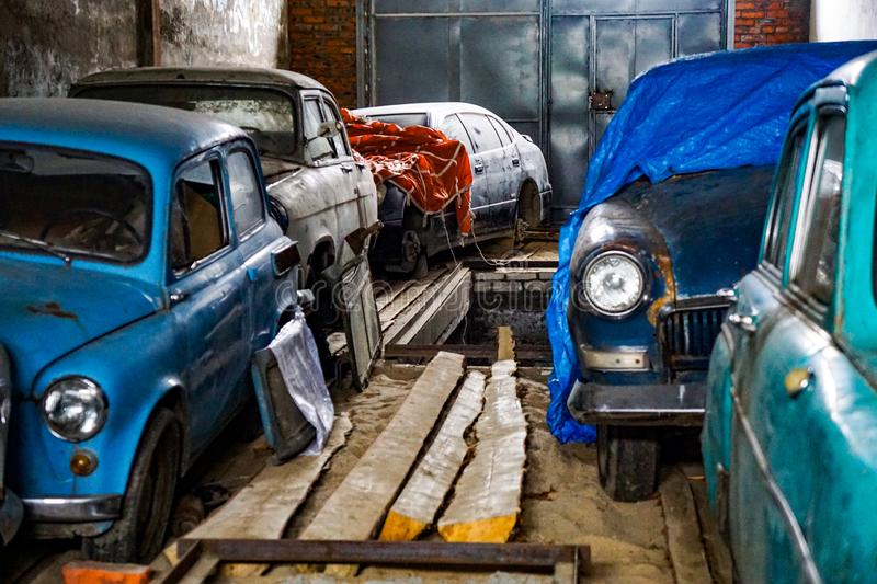 Many old cars since the Soviet Union in the garage. USSR auto collection, retro cars, vintage in the old dilapidated room stock photos