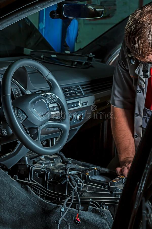A mechanic repairs a luxury SUV Repair wiring, gearboxes, disassembled interior premium crossover. Removed chairs. Leather. Interior. Neat repair service center stock images