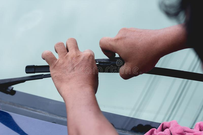 Mechanic replace windshield wipers on car. Replacing wiper blades royalty free stock photo