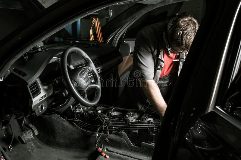 Moscow. November 2018. A mechanic repairs an Audi ... Repairing wiring, gearboxes, disassembled interior premium crossover. Removed chairs. Leather interior stock images