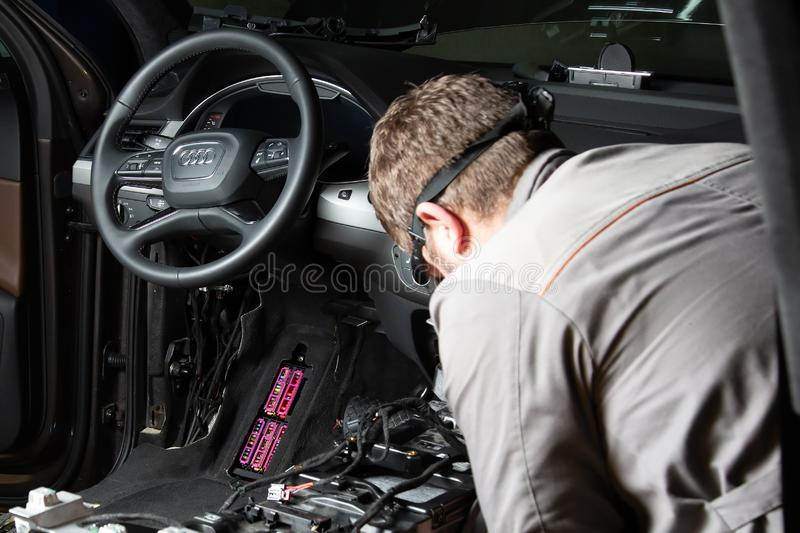 Moscow. November 2018. A mechanic repairs an Audi ... Repairing wiring, gearboxes, disassembled interior premium crossover. Moscow. November 2018. A mechanic stock photos