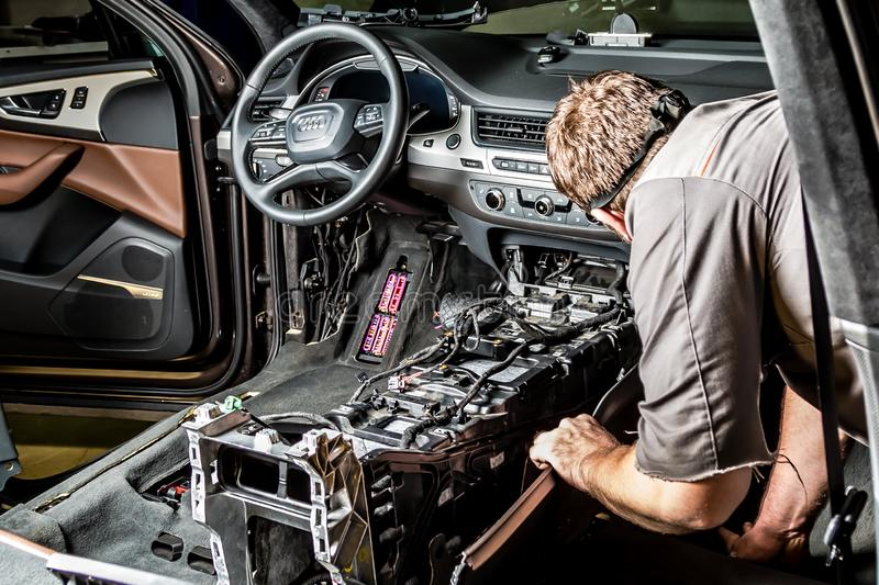 Moscow. November 2018. A mechanic repairs an Audi ... Repairing wiring, gearboxes, disassembled interior premium crossover. Removed chairs. Leather interior stock photos