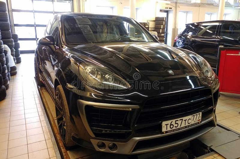 Moscow, Russia - April 29, 2019: Exclusive black Porsche Cayenne on suspension check stand in service center. Premium german SUV. With Lumma wide body kit royalty free stock images