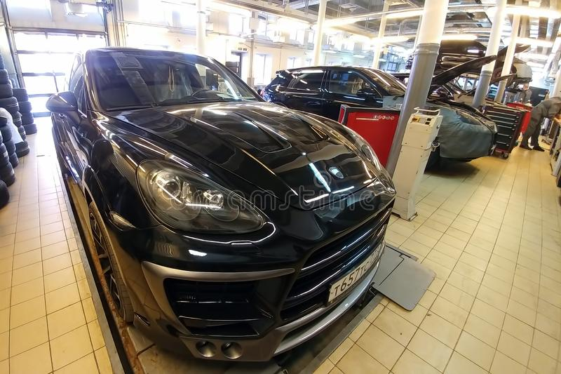Moscow, Russia - April 29, 2019: Exclusive black Porsche Cayenne on suspension check stand in service official center. Premium. German SUV with Lumma wide body royalty free stock image