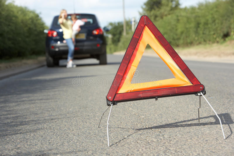 Mother And Daughter Broken Down On Country Road. With Hazard Warning Sign In Foreground royalty free stock images