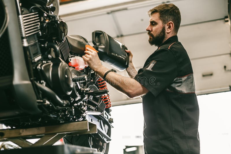 Motorcycle mechanic replacing and pouring fresh oil into engine royalty free stock photos