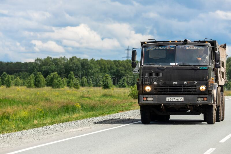Novosibirsk/ Russia – June 27 2020: Big dirty truck Kamaz. Novosibirsk/ Russia – June  27 2020:  Big dirty truck Kamaz moving on the highway, against the royalty free stock images