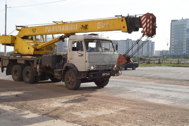Kamaz and Crane Driving on Road. Old aged Kamaz vehicle with crane attachment moves along an empty road in Russia royalty free stock photography