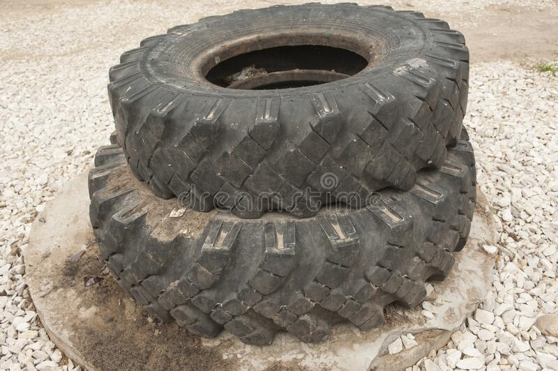 Old car tires from a KAMAZ truck. They are used in Russia to enclose wells or fences.Tires are changed in Russia twice a year-in summer and winter.The quality royalty free stock image