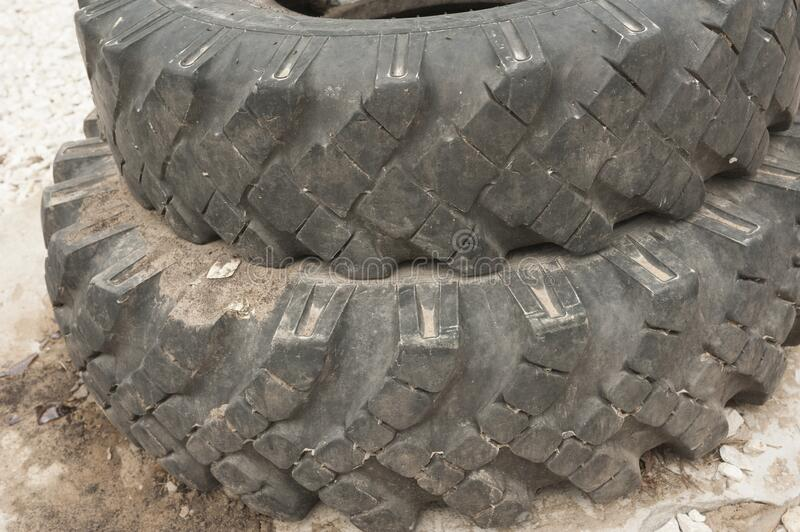 Old car tires from a KAMAZ truck in Russia. Old car tires from a KAMAZ truck.They are used in Russia to enclose wells or fences.Tires are changed in Russia twice royalty free stock photo