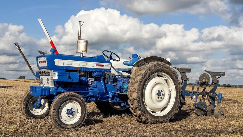 Old ford 4000 tractor ploughing. Old vintage blue ford 4000 tractor ploughing at ploughing match show. cloudy sky royalty free stock images