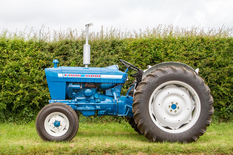 Old ford 4000 tractor. Old vintage blue ford 4000 tractor parked on grass with hedge royalty free stock images