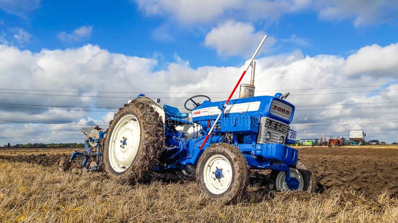 Old ford 4000 tractor ploughing. Old vintage blue ford 4000 tractor ploughing at ploughing match show royalty free stock photography
