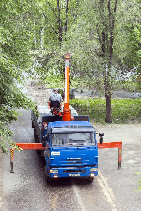 An onboard KAMAZ car with a crane manipulator performs unloading during road repair. On a city street stock image