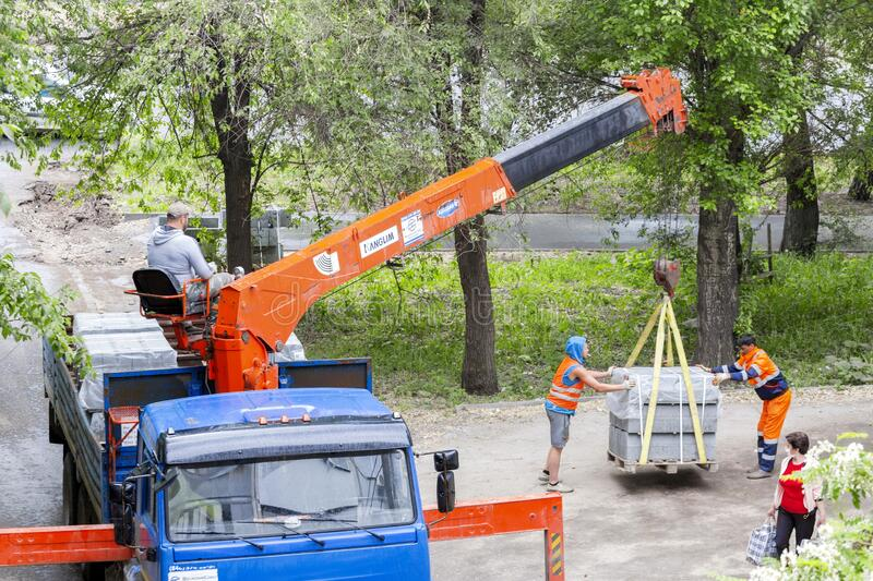 An onboard KAMAZ car with a crane manipulator performs unloading during road repair. On a city street stock images