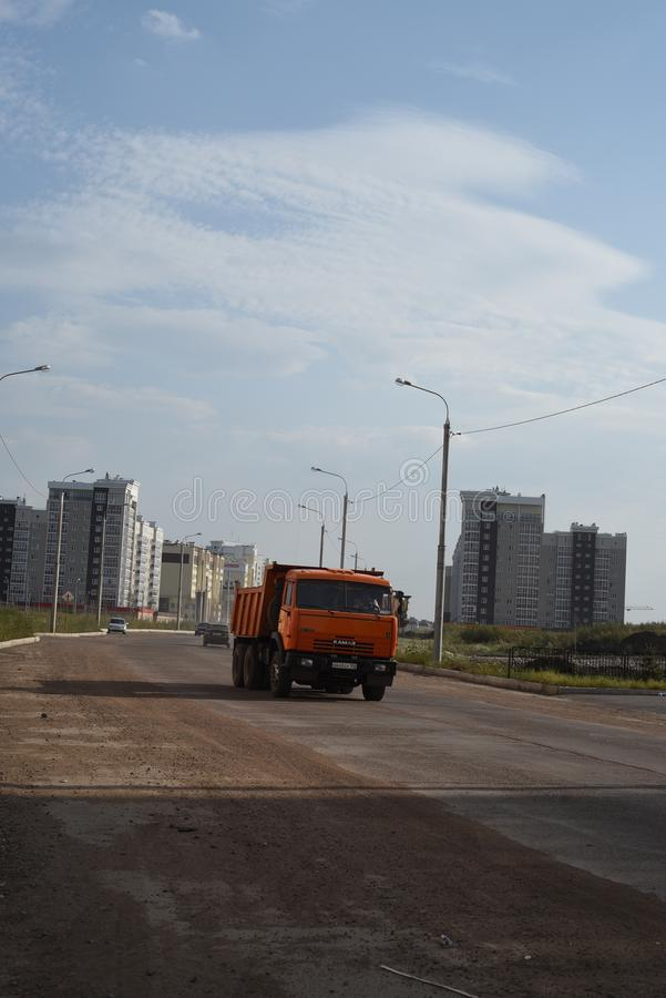Orange Russian Kamaz Vehicle on Road. Modern Russian Kamaz vehicle travels along an empty Russian road or street in a newly developed housing project royalty free stock photo