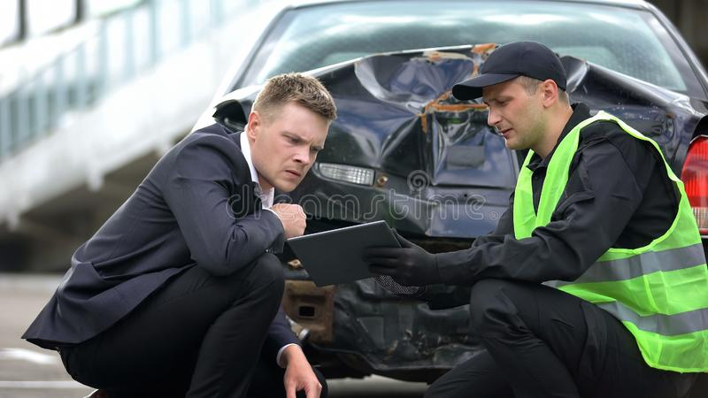Patrol worker showing driver online tablet report, modern technology, accident royalty free stock photos