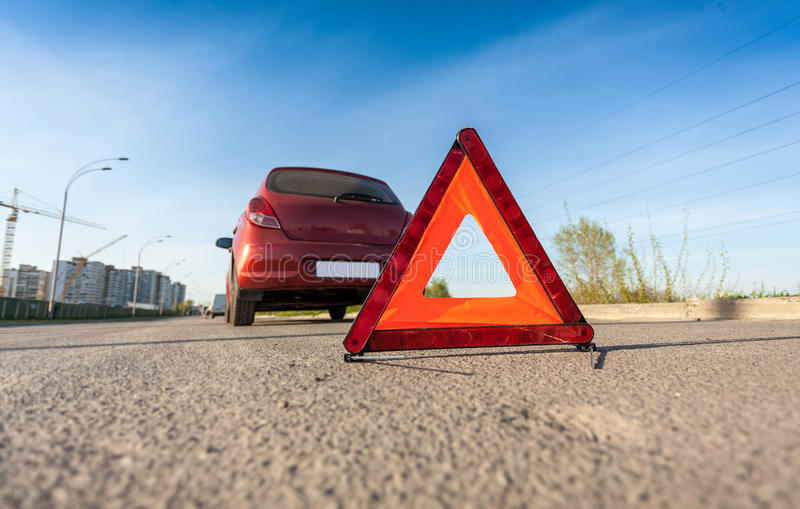 Photo of red triangle sign on road next to broken car. Closeup photo of red triangle sign on road next to broken car royalty free stock images