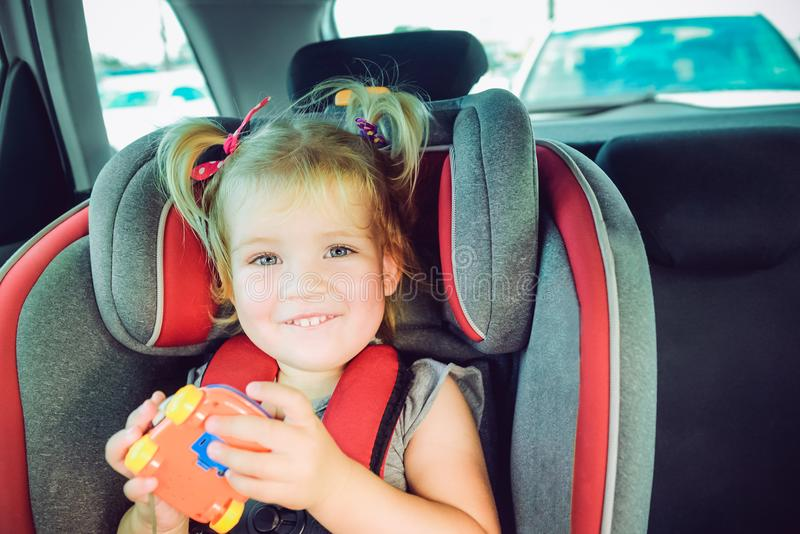 Portrait of smiling little blondy girl looking at camera and sitting in baby car seat. Child fastened with security be