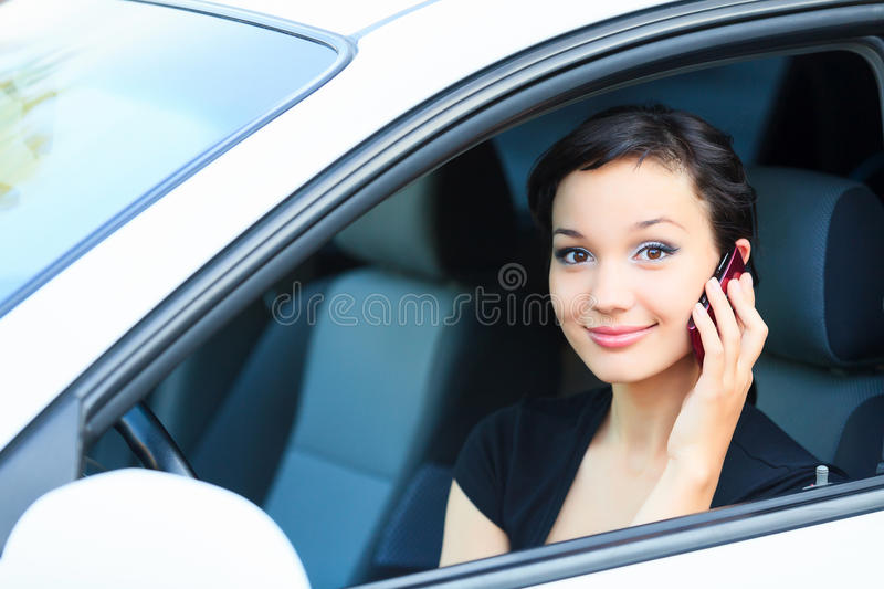 Pretty asian girl in a car. Talking by mobile telephone and smiling royalty free stock photography