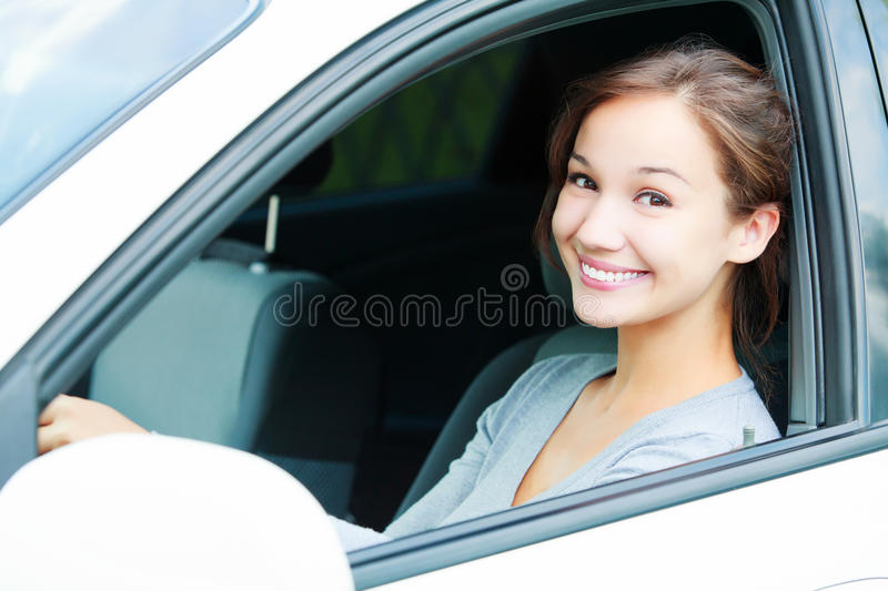 Pretty girl in a car. Smiling to you royalty free stock photo