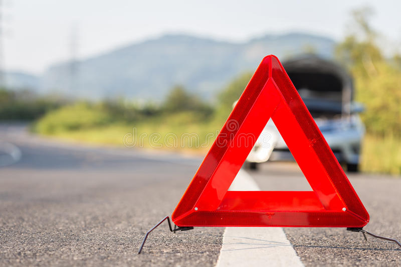 Red emergency stop sign and broken car on the road. Red emergency stop sign and broken silver car on the road royalty free stock image