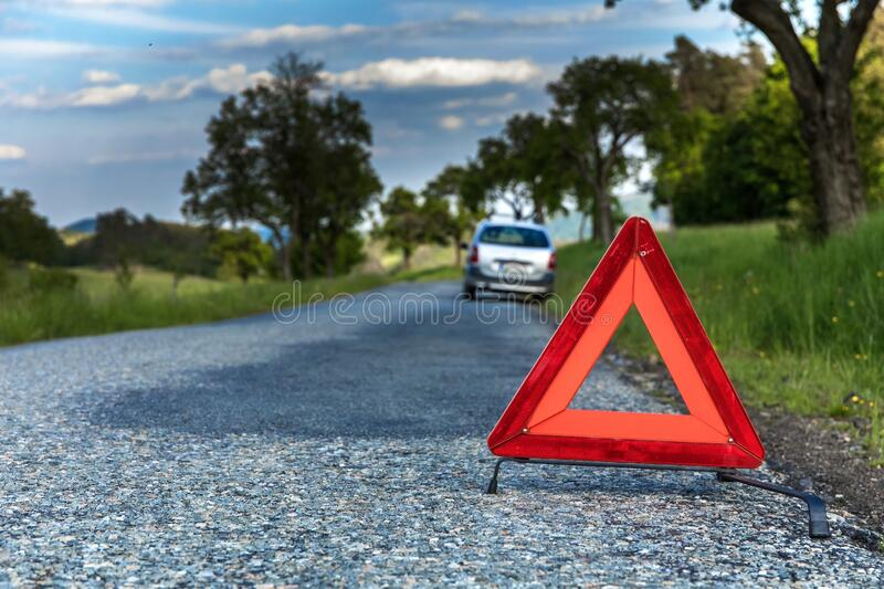 Red emergency stop sign and broken silver car on the road. Warning triangle on a country road in the Czech Republic.  royalty free stock photos