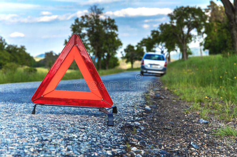 Red emergency stop sign and broken silver car on the road. Warning triangle on a country road in the Czech Republic.  stock photo