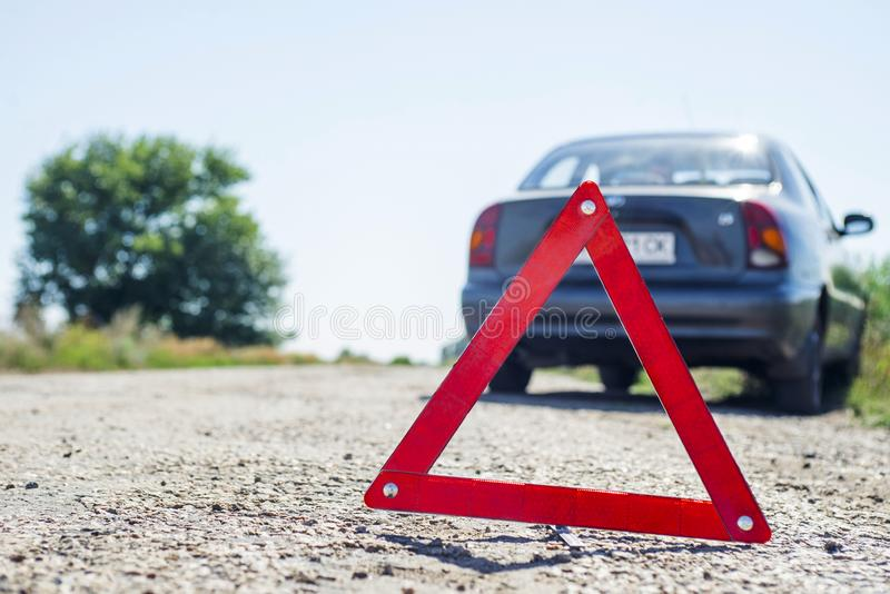 Red warning triangle with a broken down car. Red emergency stop sign and broken car on the road.  stock photo
