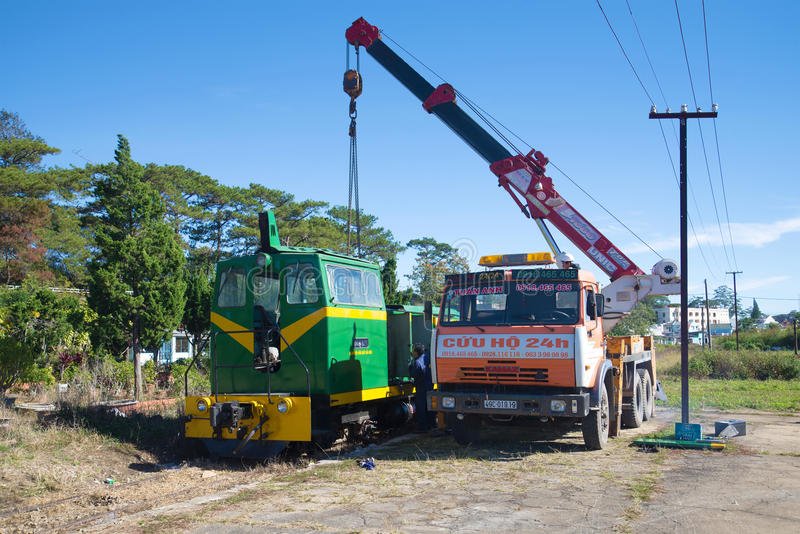 Renovation of the locomotive with the aid of the crane on the chassis of Russian Kamaz-64112 car at the railway station of Dalat. DALAT, VIETNAM - DEC 27, 2015 royalty free stock photography