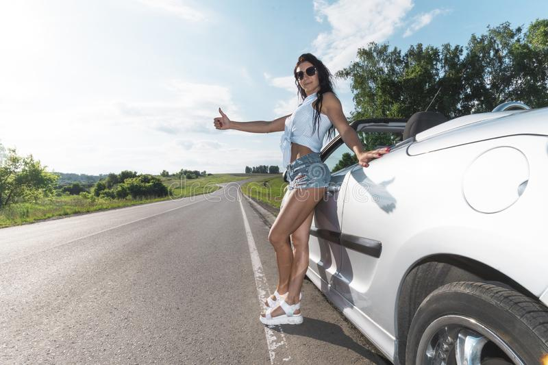 Road scene: sexy brunette girl standing near their broken car and hitchhiking. Rear view. ran out of gas. Problems with. Cars on the road. Broken car. The girl royalty free stock photos