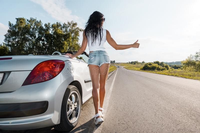 Road scene: sexy brunette girl standing near their broken car and hitchhiking. Rear view. ran out of gas. Problems with. Cars on the road. Broken car. The girl royalty free stock images