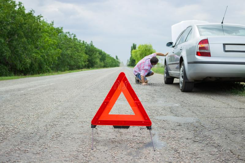 Road sign, emergency and traffic concept - warning triangle over broken car.  stock images