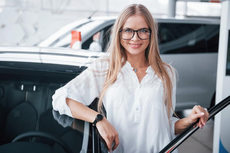 It`s her birthday gift. Cute girl in eyewear stands near the car in auto saloon. Probably her next purchase.  stock photography