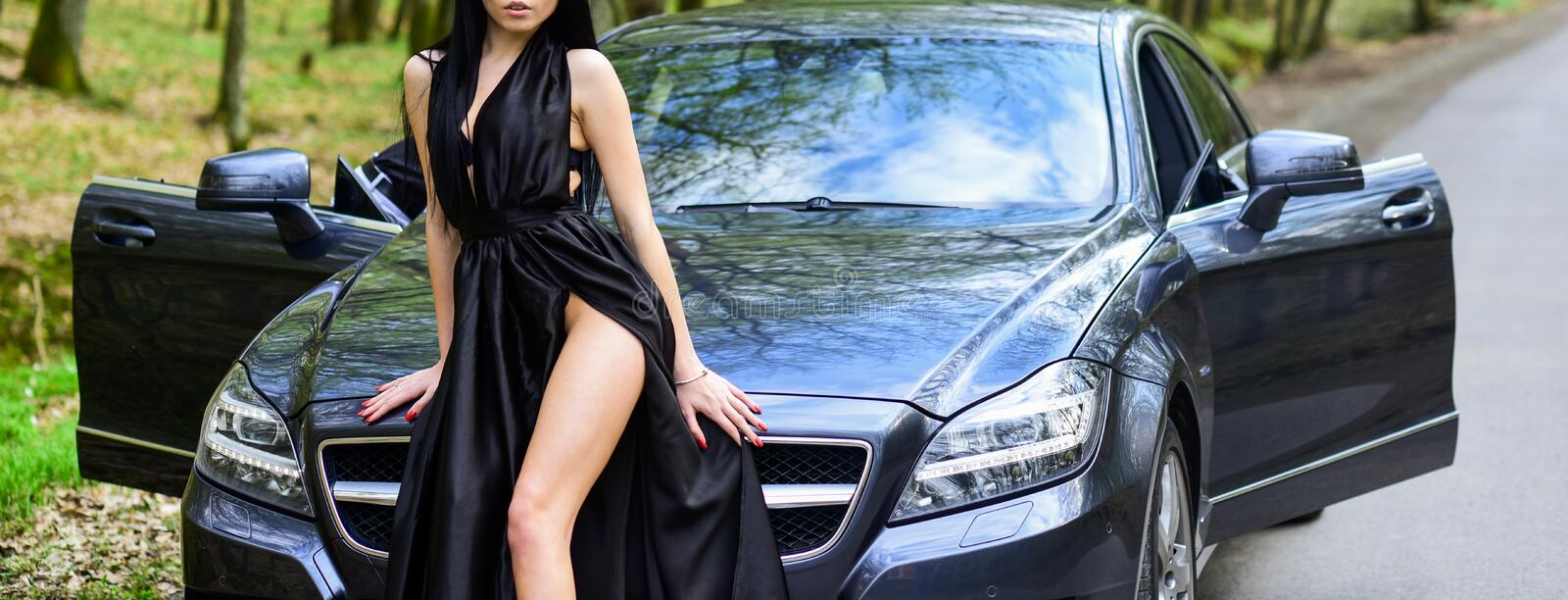 Seductive pose. Sex in car. Driver girl. Beauty and fashion. Woman in black dress escort service worker. Sexy girl. Elegant dress and auto. Provocative concept stock image