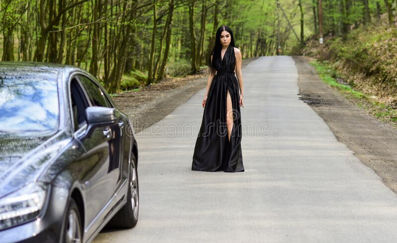 Sexy girl elegant dress at road. Escort concept. Glamorous girl and luxury car. Escort and sexual services. Driver girl. Beauty and fashion. Woman in black stock photos
