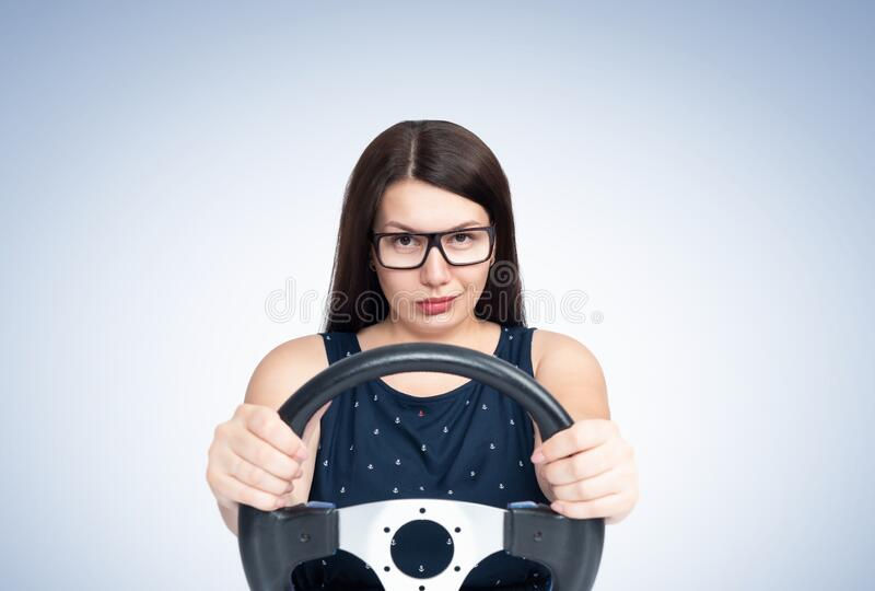 Sexy young smiling happy girl with glasses driving a car, front view.  royalty free stock image