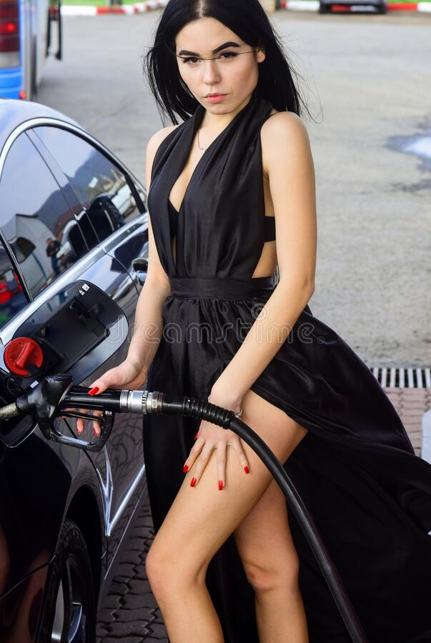 Because someone has to do it. Sexy girl fill car with gasoline. Gas filling. Sensual woman at gas station. Gas and. Diesel fuel. Transport and transportation royalty free stock images