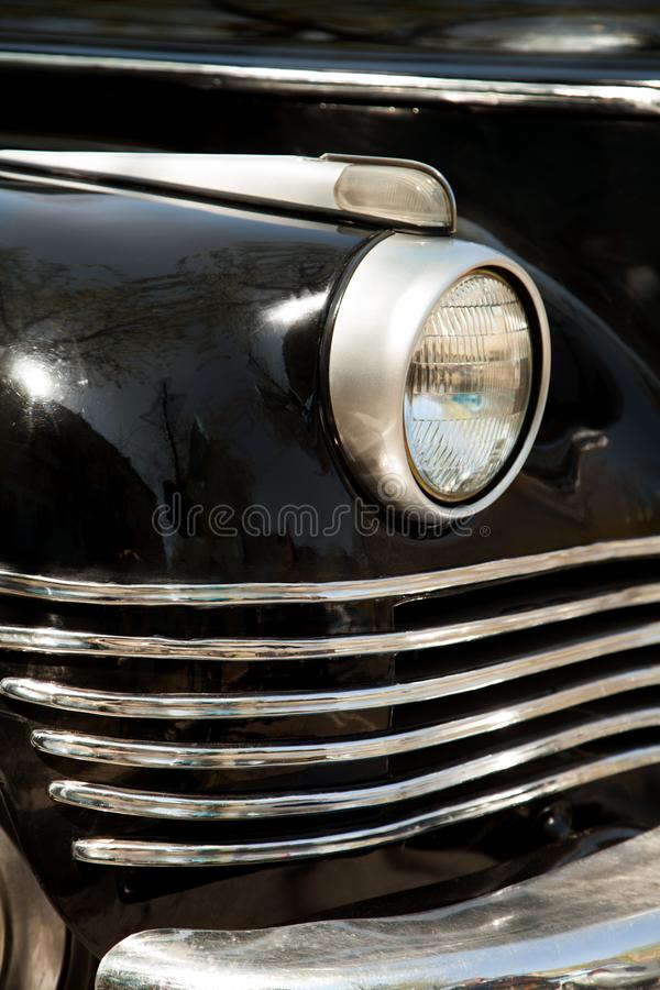 Soviet black retro car ZIS front close-up. A headlight and a radiator grille detail of a vintage USSR auto royalty free stock photography