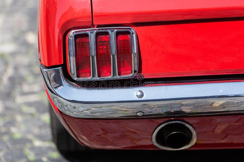 Tail light of an old Ford Mustang. Bottrop, Germany - June 07, 2019: tail light of an old Ford Mustang. The Ford Mustang series was introduced in 1964 and was stock photography