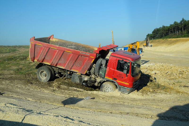 A dump truck kamaz got stuck in the mud on the side of the road. Taman, Russia - June 9, 2019: A dump truck kamaz got stuck in the mud on the side of the road royalty free stock image
