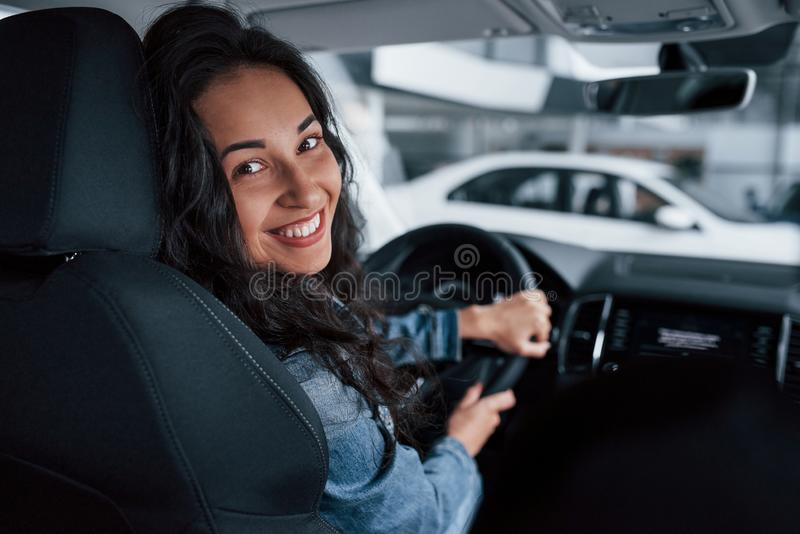 Toothy smile. Cute girl with black hair trying her brand new expensive car in the automobile salon.  royalty free stock photo
