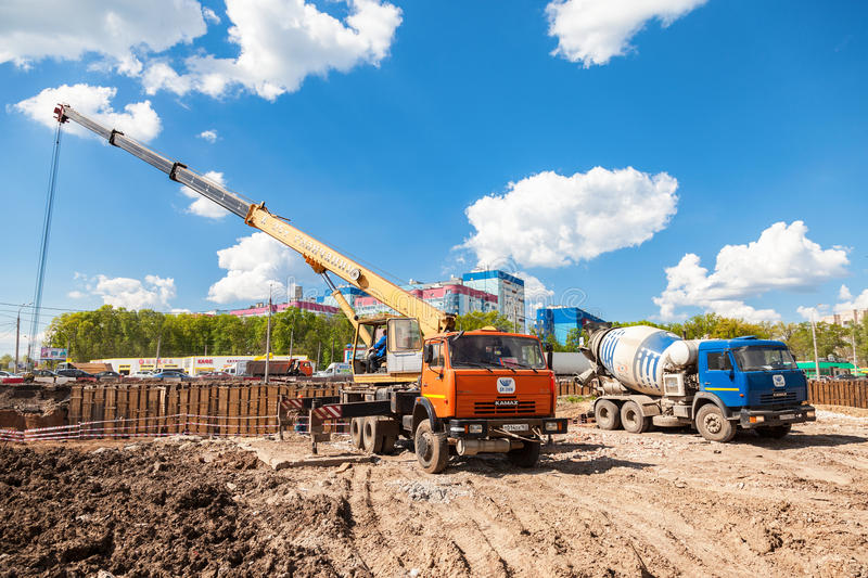 Truck crane KAMAZ and concrete mixer truck. SAMARA, RUSSIA - MAY 7, 2016: Truck crane KAMAZ and concrete mixer truck working at the construction site under stock photos