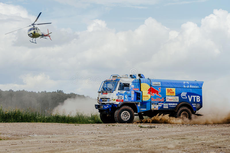Truck rally truck KAMAZ on dust road with a flying helicopter. Filimonovo, Russia - July 10, 2017: truck rally truck KAMAZ on dust road with a flying helicopter stock photos