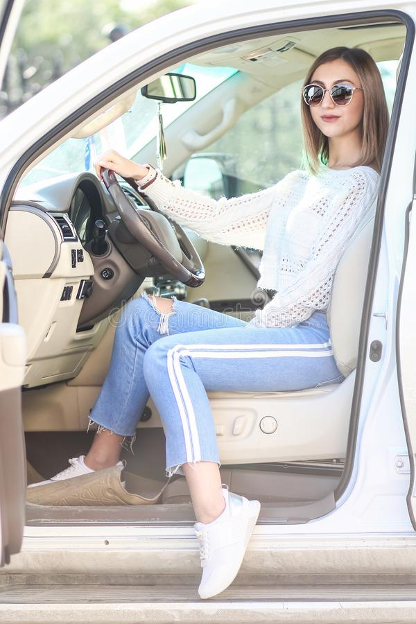 Young girl in the luxury car. Pretty young girl in a casual clothes sitting in the modern luxury off-road car royalty free stock image